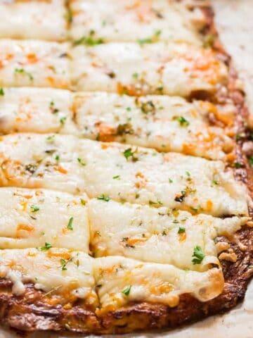 cheesy cauliflower breadsticks served with spicy marinara sauce