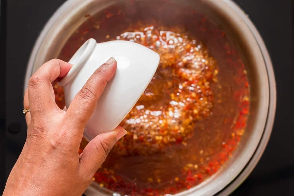 cooking homemade spicy sweet chili sauce in pan