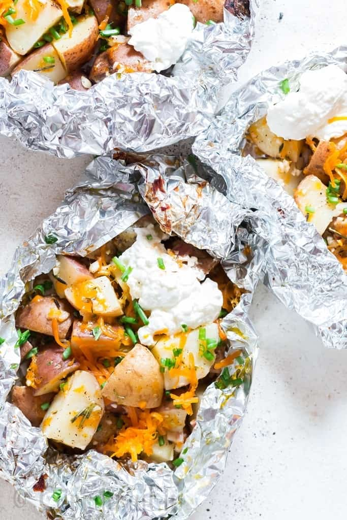 cheesy campfire grilled potatoes in foil packets with sour cream and scallions