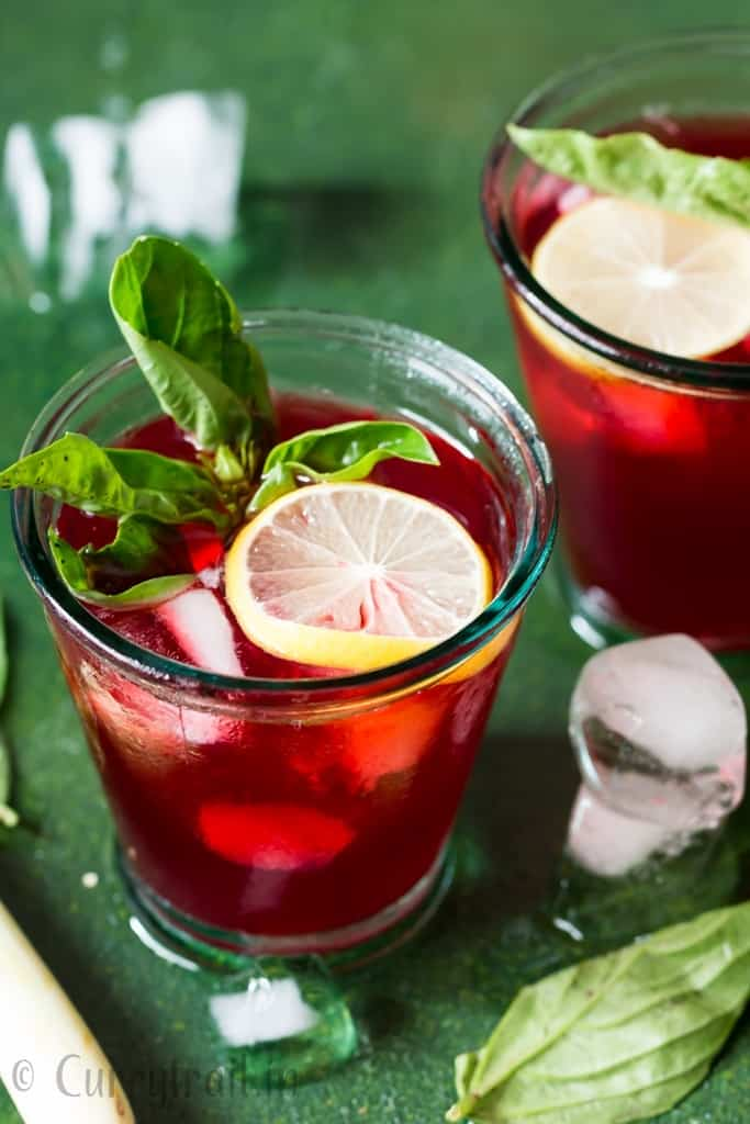 refreshing hibiscus iced tea served in glasses with basil and lemon