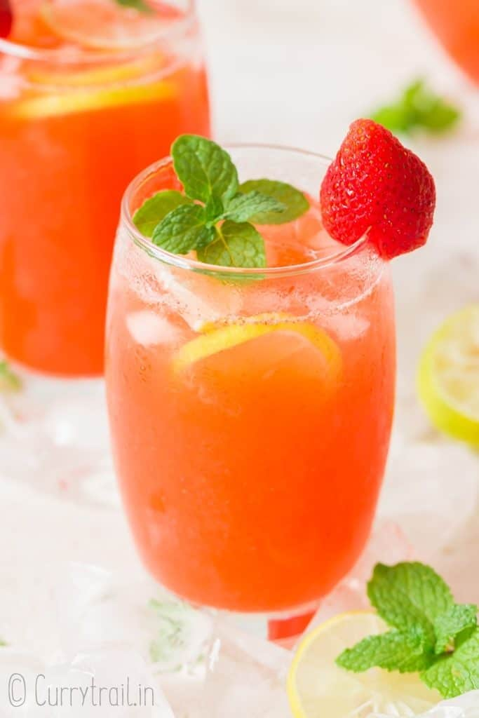 two glasses of strawberry lemonade garnished with fresh strawberry and mint leaves