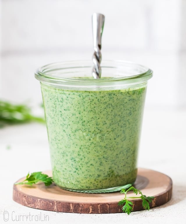 cilantro sauce served in glass weck jar with spoon in it