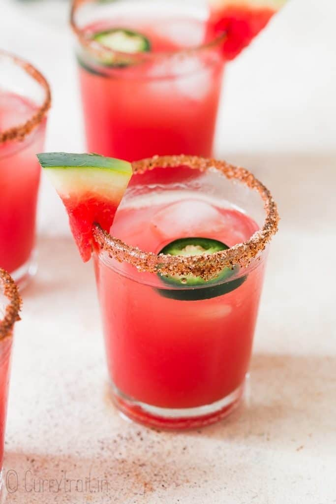 spicy watermelon margarita served in small glass with paprika salt rim