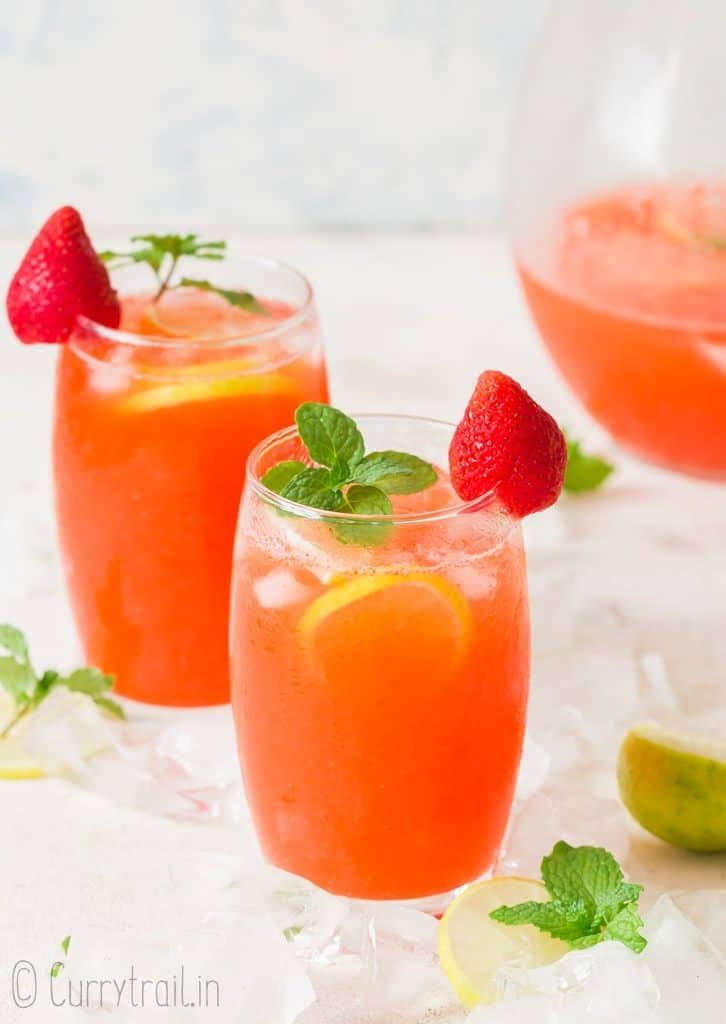 fresh strawberry lemonade served in two glasses with a pitcher on the side