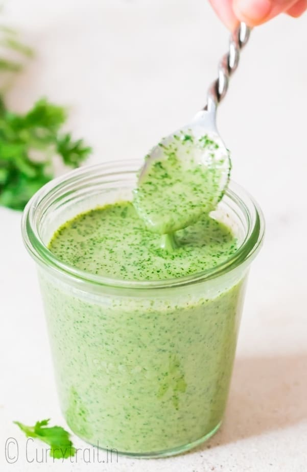 cilantro sauce in glass jar with fancy spoon