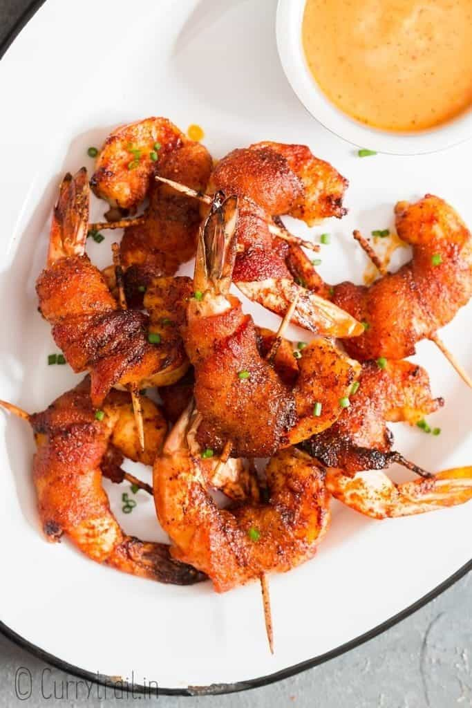 crispy bacon wrapped shrimps with spicy sauce on the side