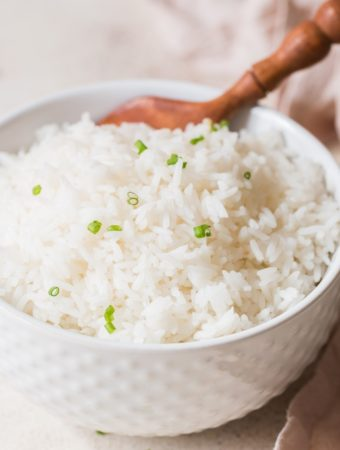 steamed rice with chives on top in white bowl with wooden spoon