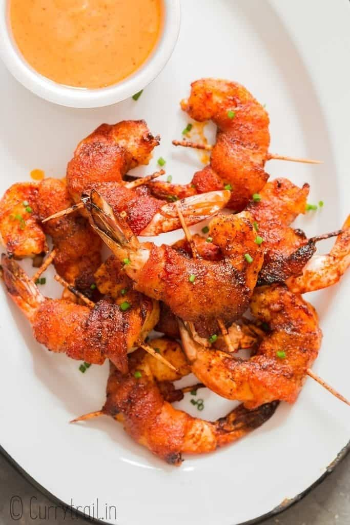 spicy sweet bacon wrapped shrimp on white plate with spicy dipping sauce