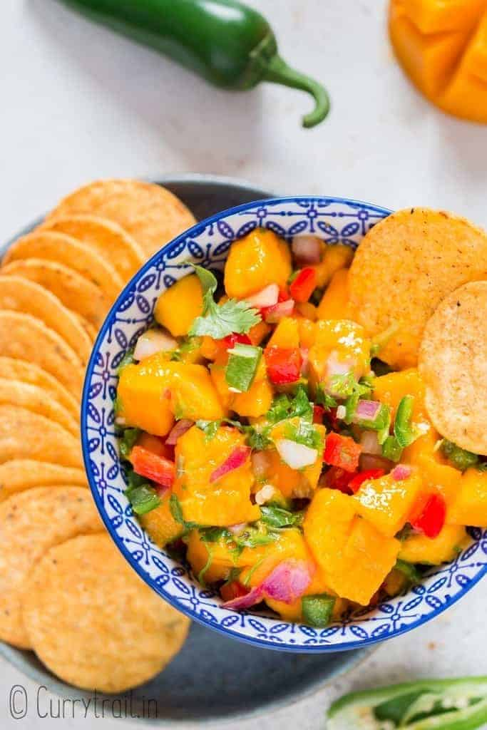 fresh salsa made with mangoes in blue ceramic bowl with nachos