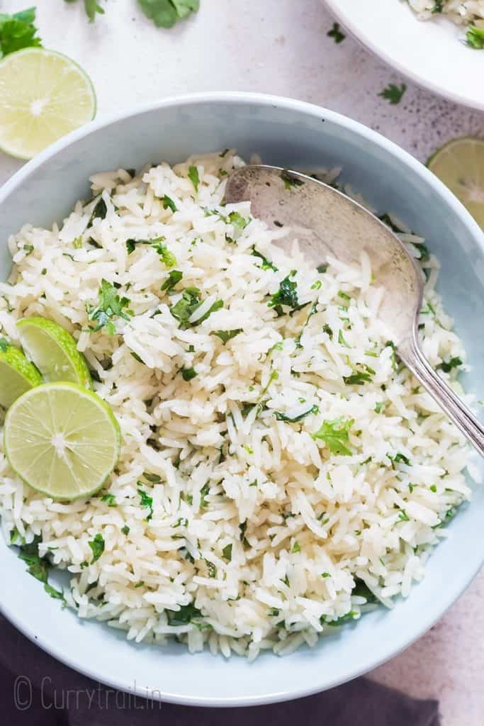 white bowl with cilantro and lime rice with lime slices on top with spoon