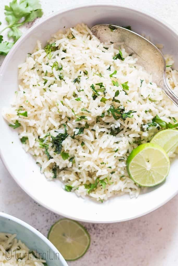 white bowl with cilantro and lime rice with lime slices on top
