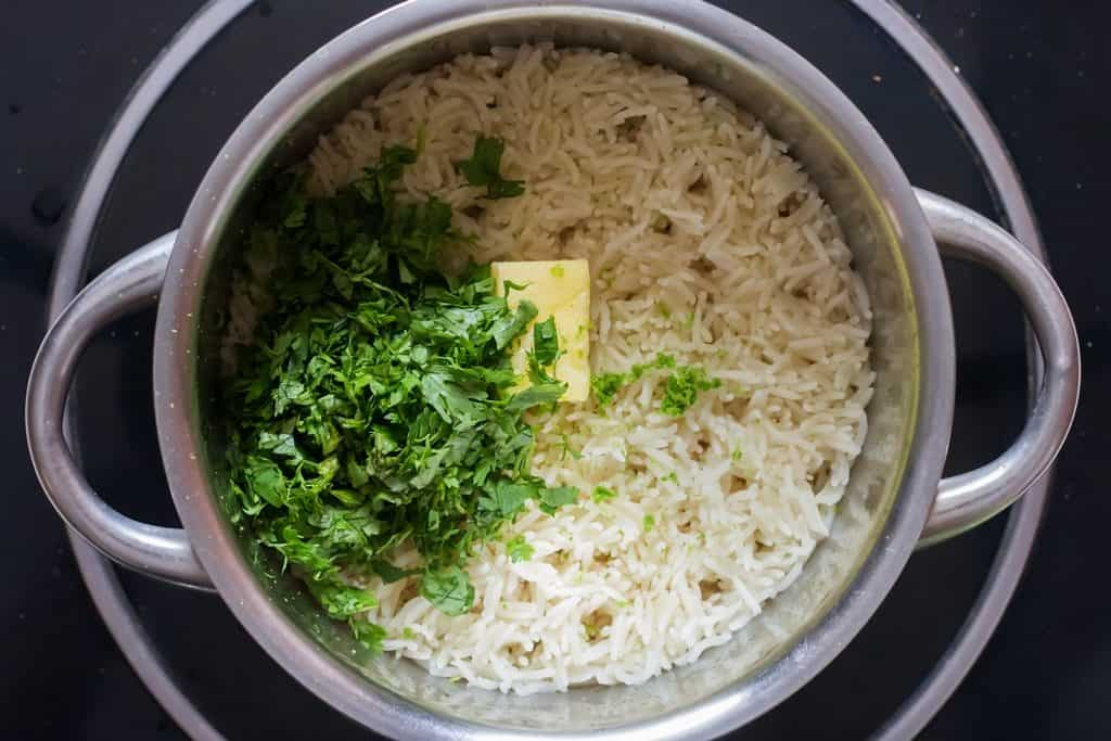 ingredients added to rice to make cilantro lime rice in deep bottom pot