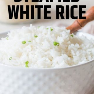 steamed rice with chives on top in white bowl with wooden spoon with text overlay
