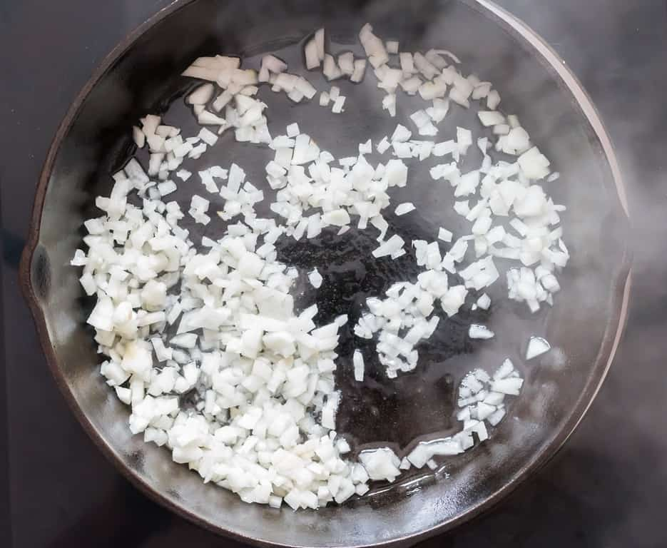 white onions sauteed in oil in cast iron pan