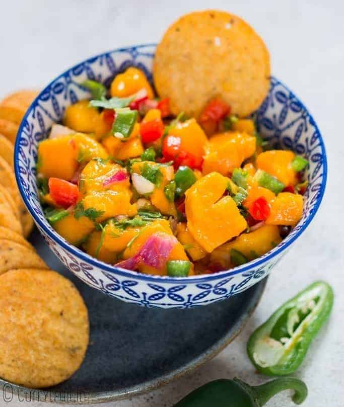 fresh summer salsa using mangoes with nachos in blue ceramic bowl