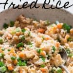 cauliflower fried rice in white bowl with text overlay