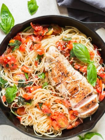 bruschetta chicken pasta in cast iron pan with napkin