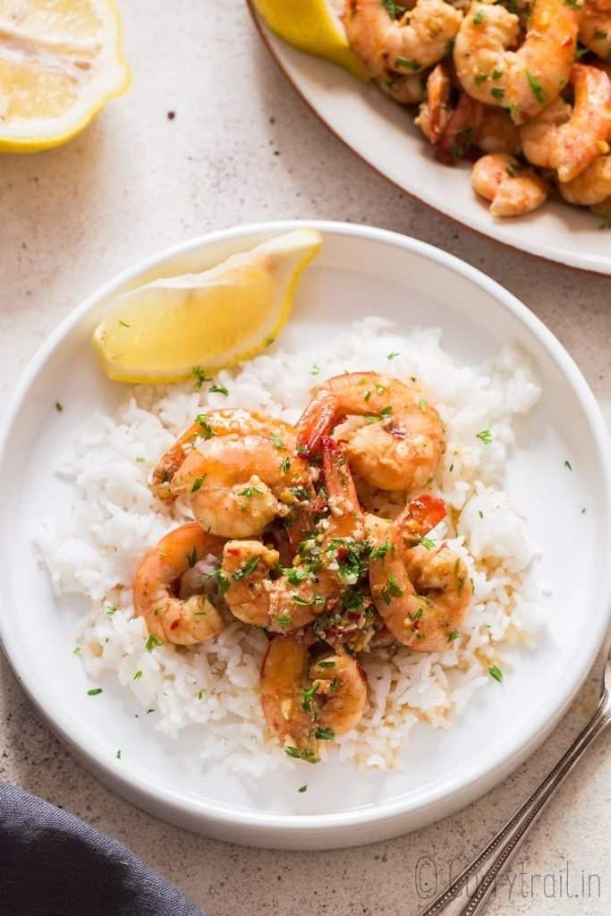 lemon garlic butter shrimp served over rice and lemon wedges on side