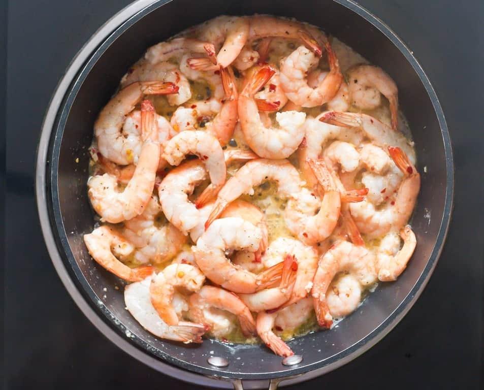 cooking lemon garlic shrimps in skillet