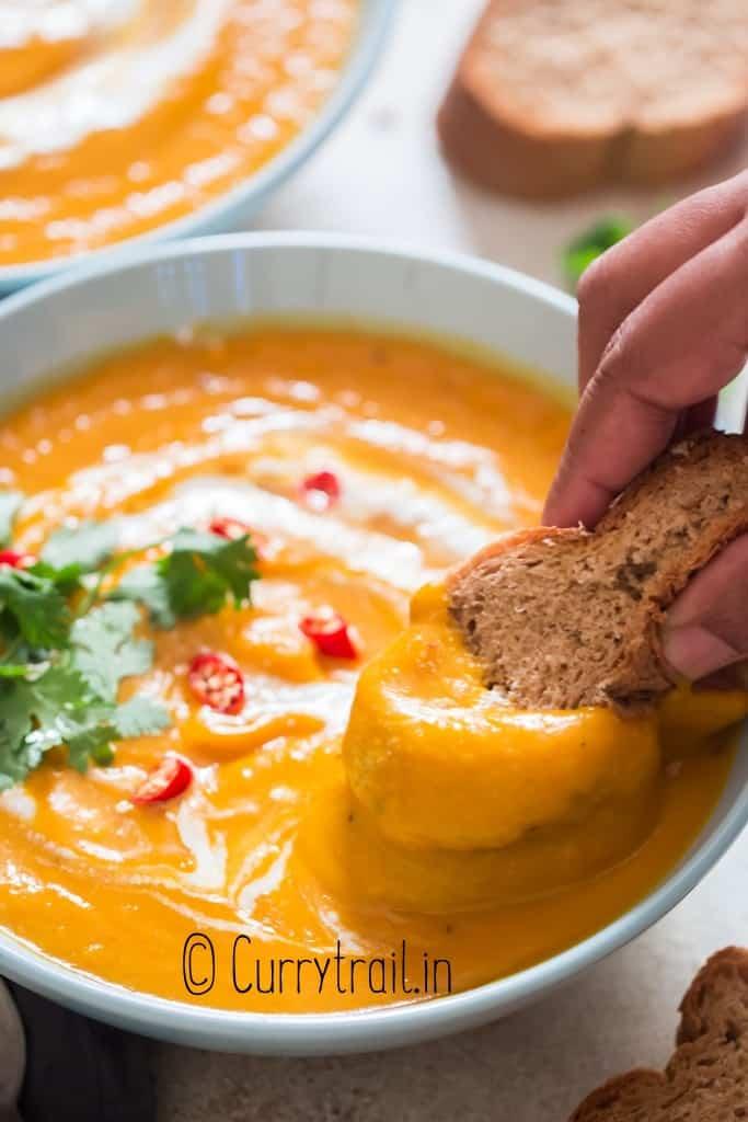 crusty bread dunked in pumpkin soup