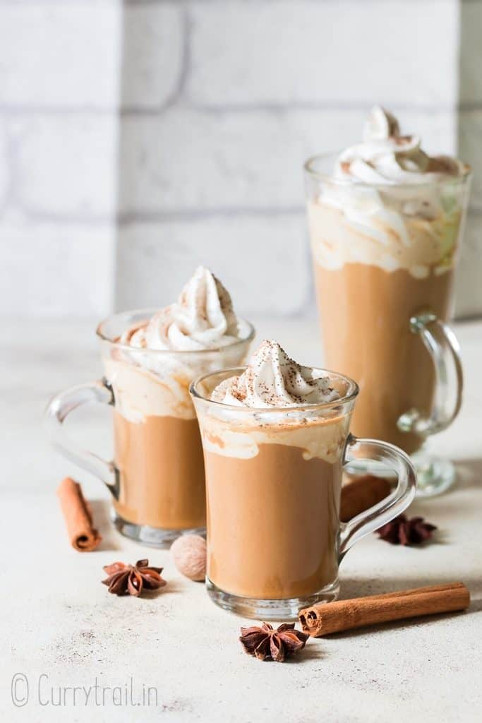 spiced latte with pumpkin served in 3 cups garnished with whipped cream and pumpkin pie spice