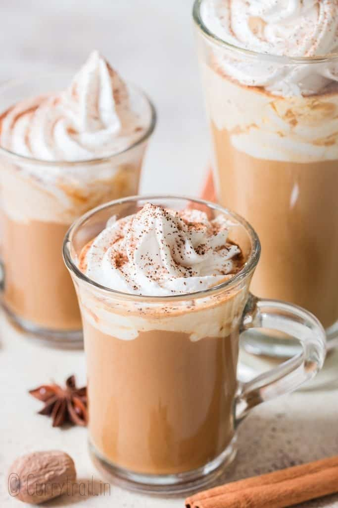 3 cups of pumpkin spice latte served with whipped cream and pumpkin pie spice on top