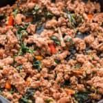 spicy Thai basil chicken in cast iron pan