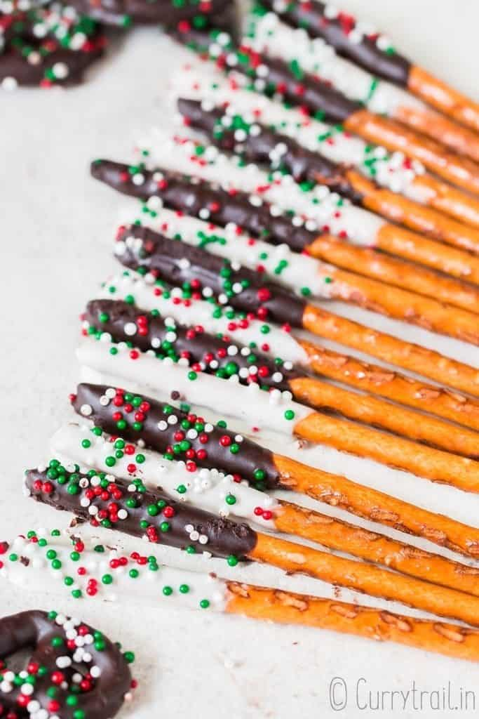 pretzels dipped in chocolate laid on parchment paper