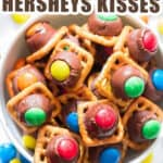 m&m pressed into hershey kisses over pretzel squares with text
