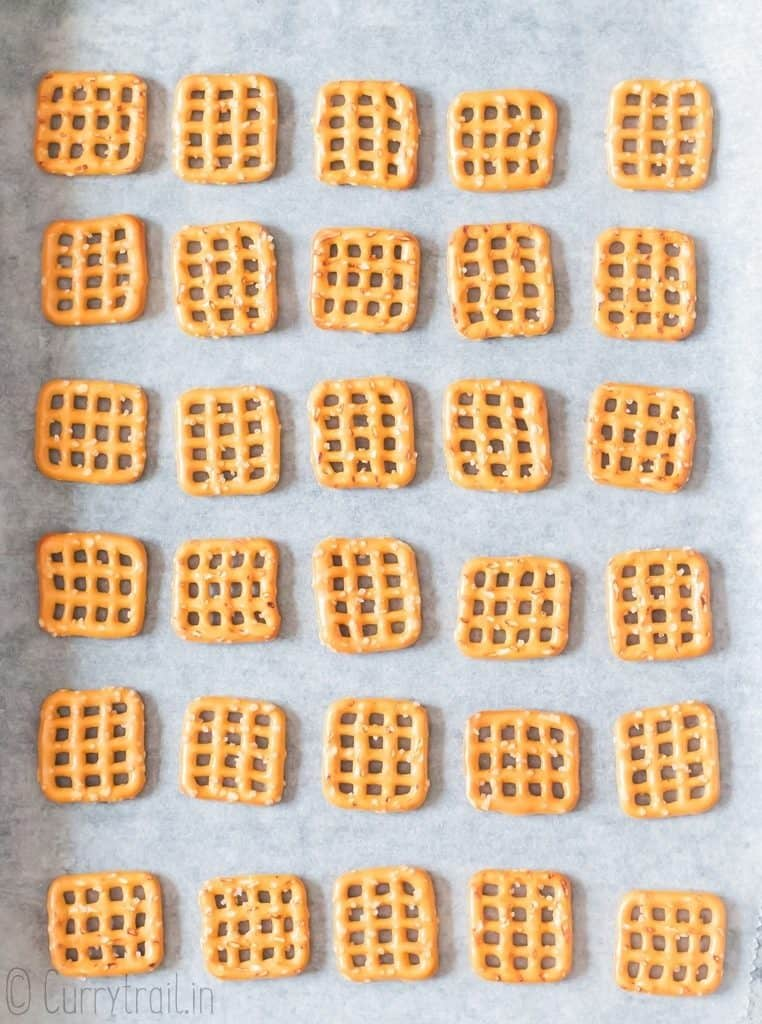 pretzel squares arranged on baking tray lined with parchment paper