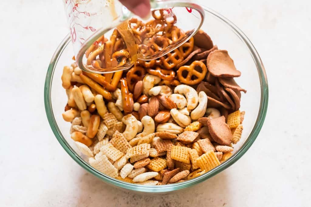 adding seasoning to chex mix bowl