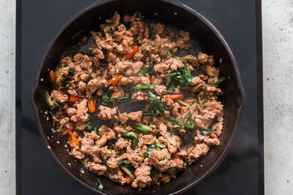 cooking Thai basil chicken in pan