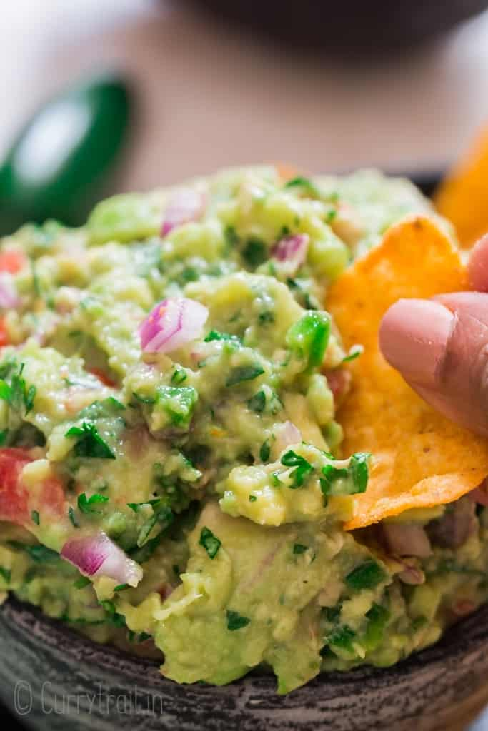 homemade guacamole with nachos scooping the dip