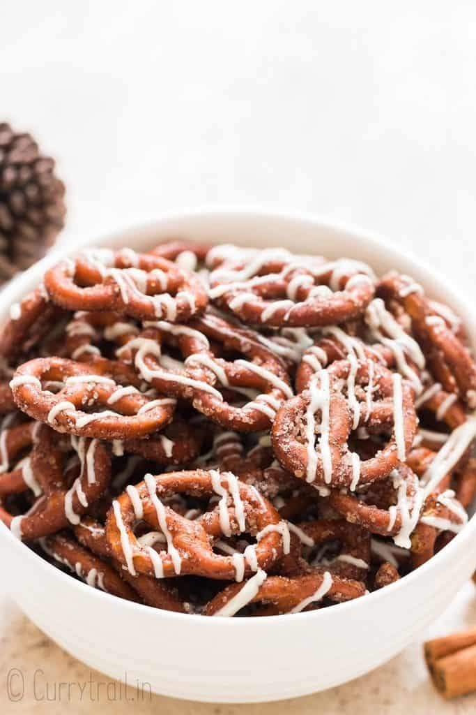 white chocolate drizzed cinnamon pretzels in white bowl