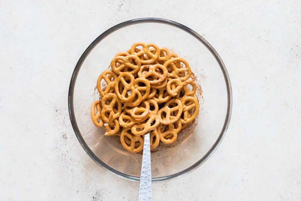 coating pretzels twists in cinnamon sugar