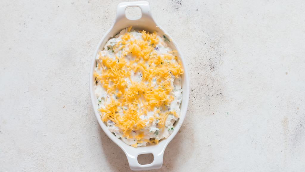 cheddar cheese sprinkled over cream cheese dip in casserole dish