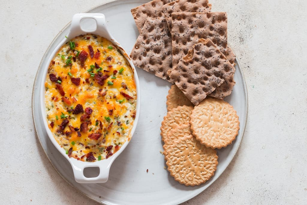 hot and bubbly cream cheese dip in casserole dish garnished with bacon and scallions