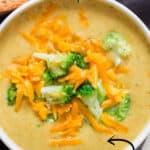 Broccoli and cheddar soup served in white bowl with text overlay