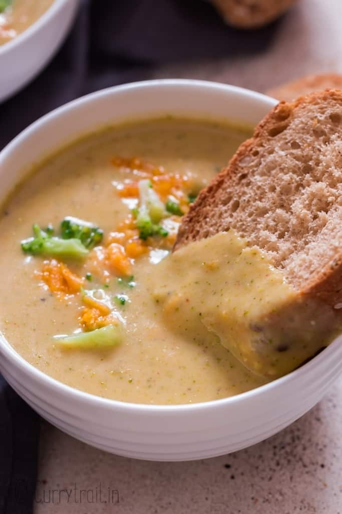 dunking crusty bread in broccoli cheddar soup
