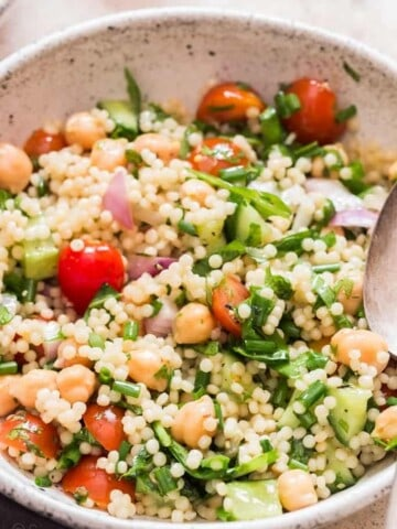 Isreali couscous salad in white bowl with spoon