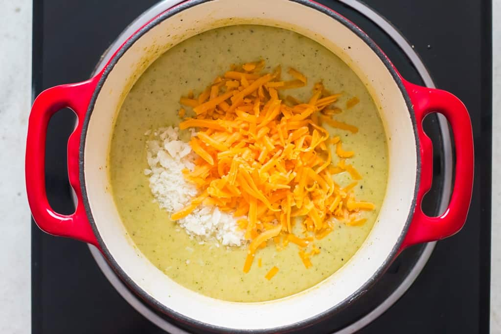 Parmesan cheese and grated cheddar cheese added to pot of hot broccoli and cheddar soup