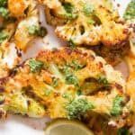 oven roasted cauliflower steaks served with chimichurri sauce on white plate