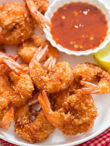 crispy coconut shrimp with sweet chili sauce for dipping on white plate