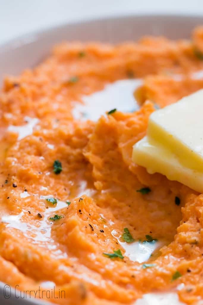 close up of mashed sweet potatoes served with cubed butter in white bowl