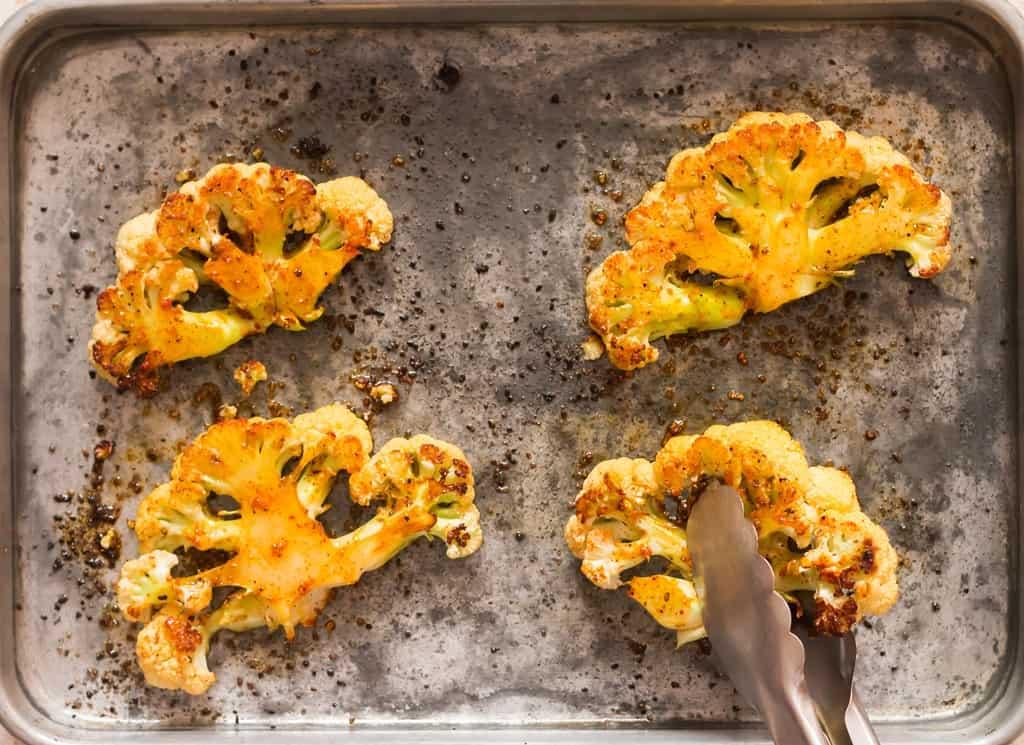 flipping roasted cauliflower steaks on baking tray