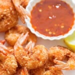 crispy coconut crusted shrimp with red chili sauce for dipping with text