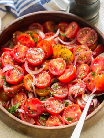 summer cherry tomato salad served in wooden salad bowl with pepper mill on side
