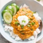 red lentil curry served over bowl of rice and garnish with cilantro