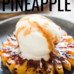 grilled pineapple served with vanilla ice cream and brown sugar rum glaze on ceramic plate
