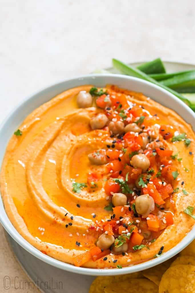 creamy roasted red pepper hummus made from scratch served in ceramic bowl with veggies and chips on sides